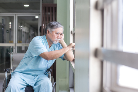 Asian old man sit on wheelchair looking out to other place. People with health care and medical concept. 스톡 콘텐츠