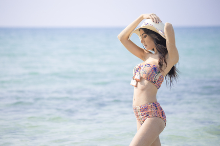 Beautiful asian woman posing at the the ocean.