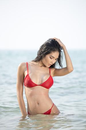 Beautiful asian woman posing at the the ocean.