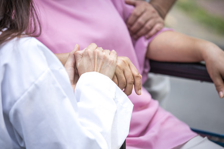 Doctor woman take care to patient at park. Doctor holding patient hand.