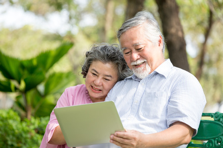 Senior People using laptop for live chat with friend at outdoor park. Elder people using laptop with attractive smiling together. People lifestyle concept.