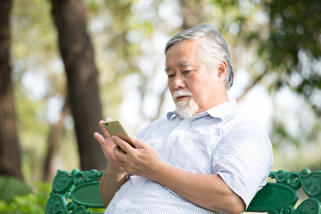 Elder people using smartphone with at park. People lifestyle concept. 스톡 콘텐츠