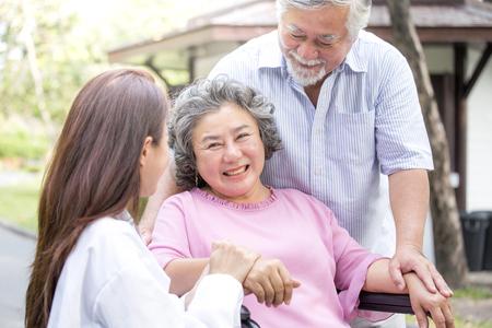 La mujer del doctor cuida al paciente mayor en el parque. Foto de archivo