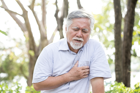 Senior asian man suffering from chest pain at outdoor place. Old man holding chest with painful feeling.