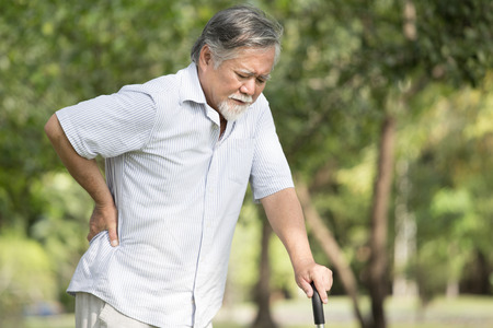 Älterer asiatischer Mann, der unter Rückenschmerzen am Platz im Freien leidet. Alter Mann, der wegen Hexenschuss zurückhält Standard-Bild