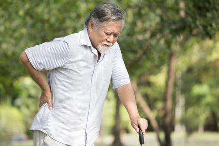 Hombre asiático mayor que sufre de dolor de espalda en el lugar al aire libre. Anciano reprimiéndose por lumbago Foto de archivo