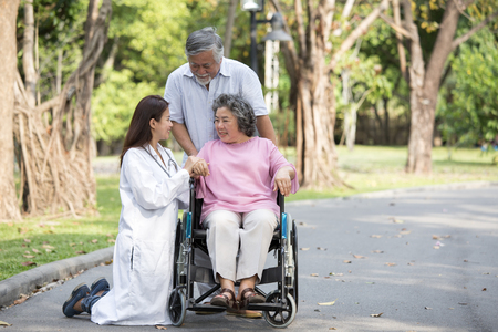 Doctor woman take care to elder patient at park.