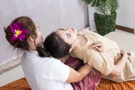 Beautiful young woman having her body with masseur in spa salon. Woman with thai massage. Woman with relax emotion. 免版税图像