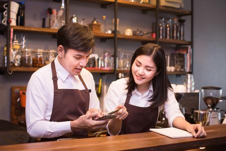 Aziatische paarbarista die in de teller van de koffiewinkel werkt. Barista die bij café werkt. Mensen die werken met de eigenaar van een klein bedrijf of het MKB-concept.