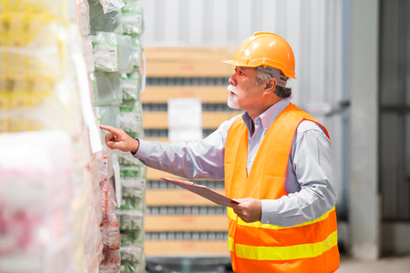 Aged male engineer working at warehouse. They Work in Industry Manufacturing Factory.