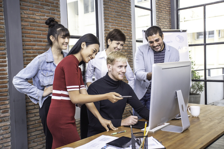 Male designer working with team for design concept at modern office. Team assist male designer to design together. Banco de Imagens