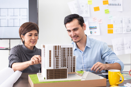 Close-up building model on table. Architect working with team with building project. Banco de Imagens