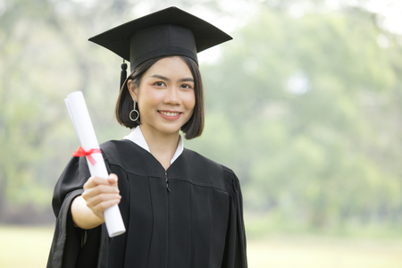 Young Asian Woman Students wearing Graduation hat and gown, Garden background, Woman with Graduation Concept. Banco de Imagens