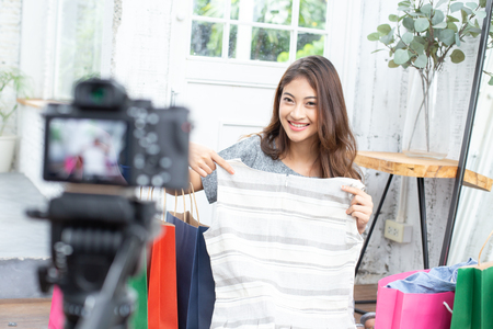 Attractive asian girl promote her business to social media. Woman using camera for present her product to social media. People with Online Business, Shopping, SME, Communication Concept.