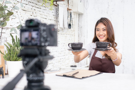 Asian barista looking to camera for live to social media. Female barista using social media to promote her shop. People with SME, Online Business, Startup Concept.