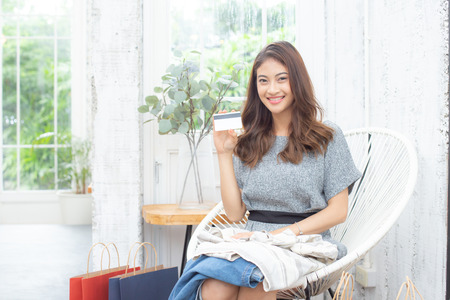 Asian attractive girl using credit card for shopping with smiling. People with shopping concept.