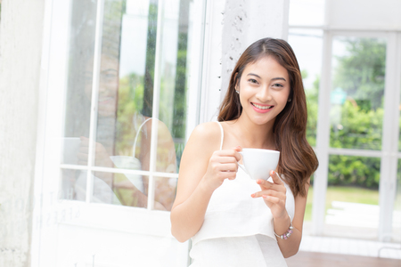 Young beautiful asian woman holding coffee with attractive smiling at home. People lifestyle concept.