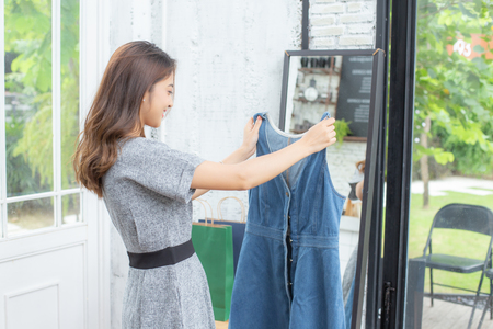 Asian attractive girl holding to dress in hand with smiling. People with shopping concept.