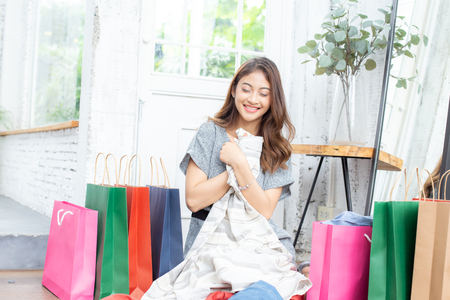 Asian attractive girl looking to clothes with smiling. People with shopping concept.