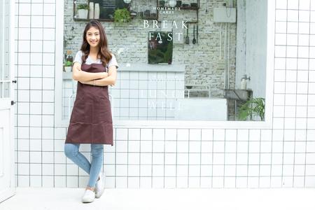 Les femmes asiatiques Barista souriant et à la recherche de l'appareil photo au comptoir du café Barista femme travaillant au café. Femme de travail propriétaire de petite entreprise ou concept de PME.