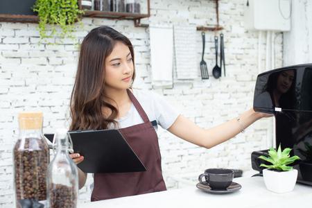 Aziatische vrouwenbarista die aan koffiemachine controleert bij couter. Barista vrouw werken bij café. Werkende vrouw kleine bedrijfseigenaar of kmo-concept. Vintage toon. Stockfoto