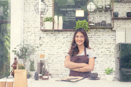 Asian Women Barista smiling and looking to camera in coffee shop counter. Barista female working at cafe. Working woman small business owner or sme concept. Vintage tone.