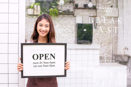 Asian Women Barista smiling and looking to camera in coffee shop counter. Barista female holding open sign in hand. Working woman small business owner or sme concept. Banco de Imagens