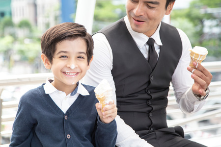 Father and Son Eating Ice Cream Together with Attractive Smile. Boy looking to Camera while Eating Ice Cream with Happy Emotion. 免版税图像