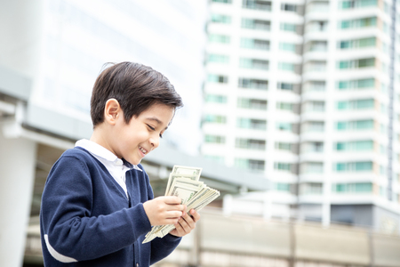 Boy carrying money with happy emotion at city background.