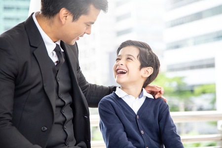 Portrait of Boy looking to father with attractive smile. Business man talking with his son with happy emotion.