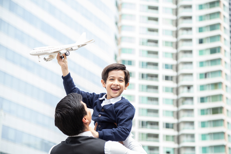 Portrait of Boy carrying airplane with attractive smile. Father holding son with happy emotion at city background. Banco de Imagens