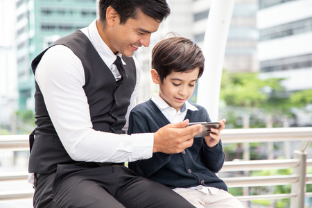 Father teaching boy to use smartphone at city. People with technology concept.
