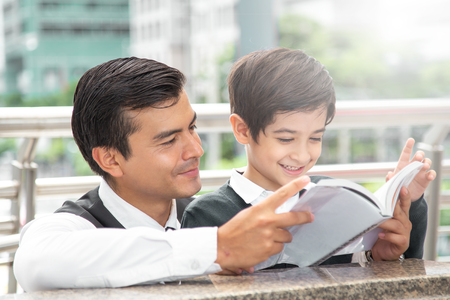 Father and Son reading book with happy emotion together. Father try to train boy about business thinking. 免版税图像