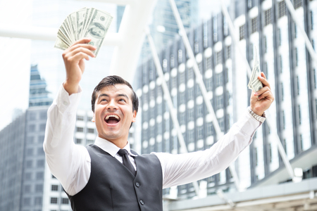 Portrait of Businessman looking to Money in hand with happy emotion.