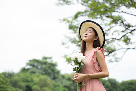 Asian attractive woman carrying flower in hand with relax emotion at garden. Women resting at garden in holiday. People with lifestyle, relax, summer, holiday concept.