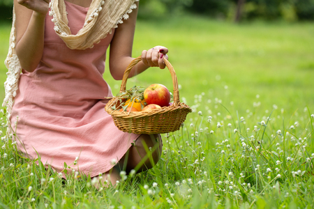 Woman holding basket in hand at garden.