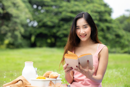 Asian attractive female holding book in her hand at garden. Women resting at garden in holiday. People with lifestyle, relax, holiday concept. 免版税图像