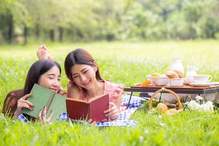 Female and friend picnic together at the public garden, Women resting at garden together in holiday. People with lifestyle, relax, holiday concept.