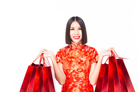 Chinese woman wear qipao and hold shopping bag in hand, isolated on white background 免版税图像