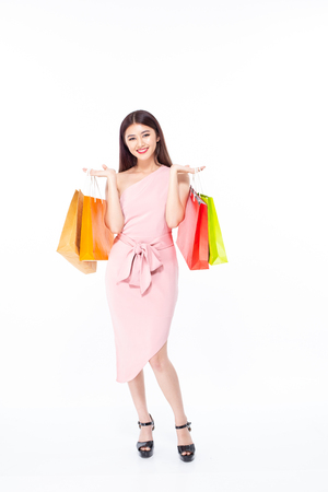 Portrait of a happy Asian beautiful woman holding shopping bags with isolated on white background. People with shopping concept. Banco de Imagens - 114332564