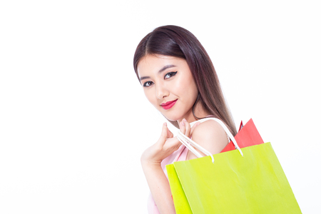 Portrait of a happy Asian beautiful woman holding shopping bags with isolated on white background. People with shopping concept.