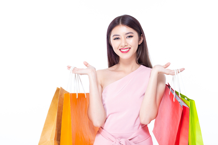 Portrait of a happy Asian beautiful woman holding shopping bags with isolated on white background. People with shopping concept. Banco de Imagens - 114332579