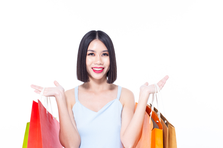 Portrait of a happy Asian beautiful woman holding shopping bags with isolated on white background. People with shopping concept. Banco de Imagens - 114332583