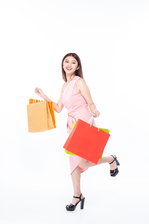 Portrait of a happy Asian beautiful woman holding shopping bags with isolated on white background. People with shopping concept. Banco de Imagens - 114332586