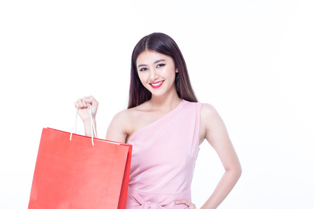 Portrait of a happy Asian beautiful woman holding shopping bags with isolated on white background. People with shopping concept. 免版税图像 - 114332587