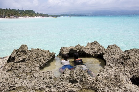 Boracay island, Philippines - August 11, 2011: two little boys are relaxing  on Boracay beach in Philippines Editoriali