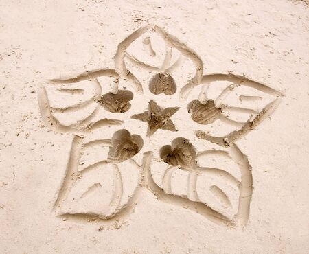 Hand drawn flower in the white sand 스톡 콘텐츠