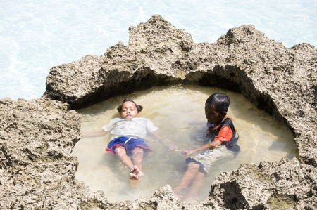 Boracay island, Philippines - August 11, 2011: two little boys are relaxing  on Boracay beach in Philippines 新聞圖片