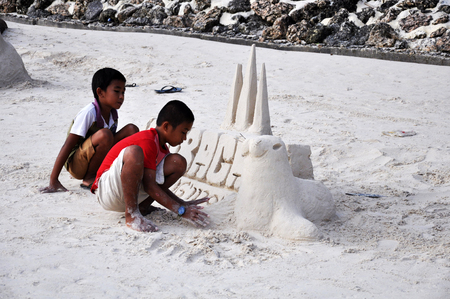 Boracay island, Philippines - August 11, 2011: two little boys are making sand tower  on Boracay beach in Philippines