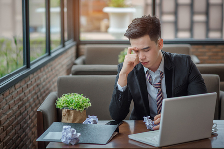 eyestrain: Portrait of an upset businessman at desk in office. Businessman being depressed by working in office. Young stressed business man feeling strain in eyes after working for long hours on compute